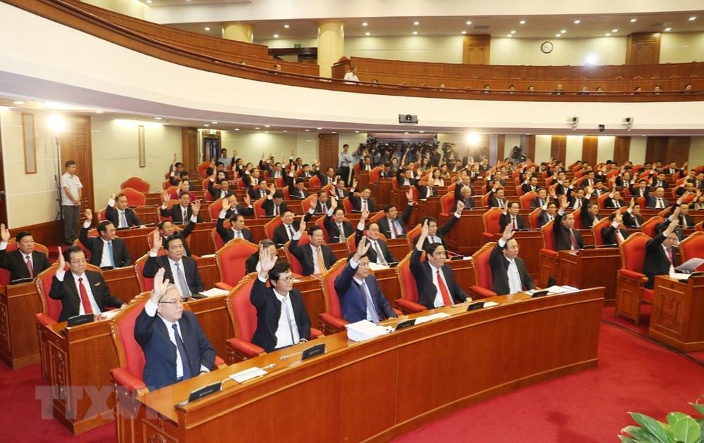 Các đồng chí lãnh đạo Đảng, Nhà nước và các đại biểu biểu quyết thông qua Nghị quyết Hội nghị lần thứ bảy. Ảnh: Trí Dũng/TTXVN