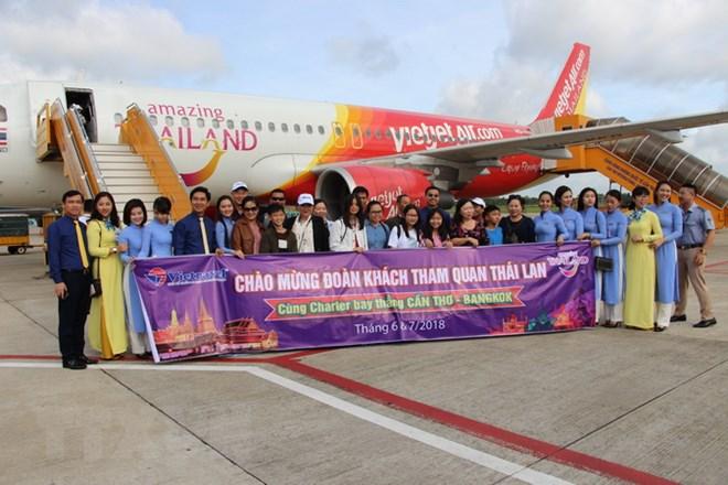 Những hành khách đầu tiên của chuyến bay Cần Thơ-B, Thái Lan chụp ảnh lưu niệm trước khi di chuyển lên máy bay. (Ảnh: Thanh Sang/TTXVN)