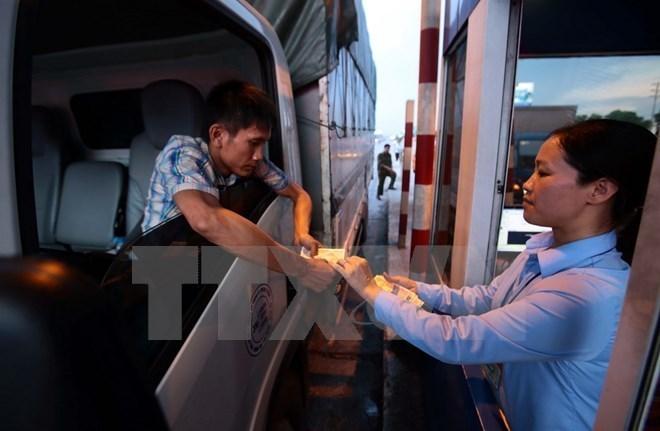 Lái xe trả tiền mua vé tại trạm thu phí BOT số 1, Quốc lộ 5 huyện Văn Lâm. (Ảnh: Phạm Kiên/TTXVN)