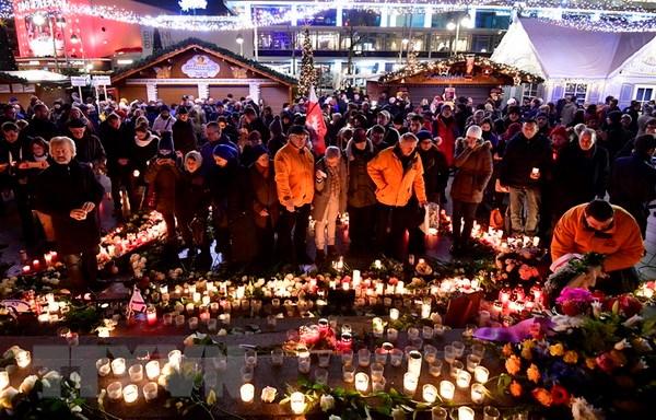 Những người tham dự thắp nến và đặt hoa trước di ảnh của những nạn nhân thiệt mạng trong vụ khủng bố, cùng cầu nguyện cho họ. (Nguồn: AFP/TTXVN)